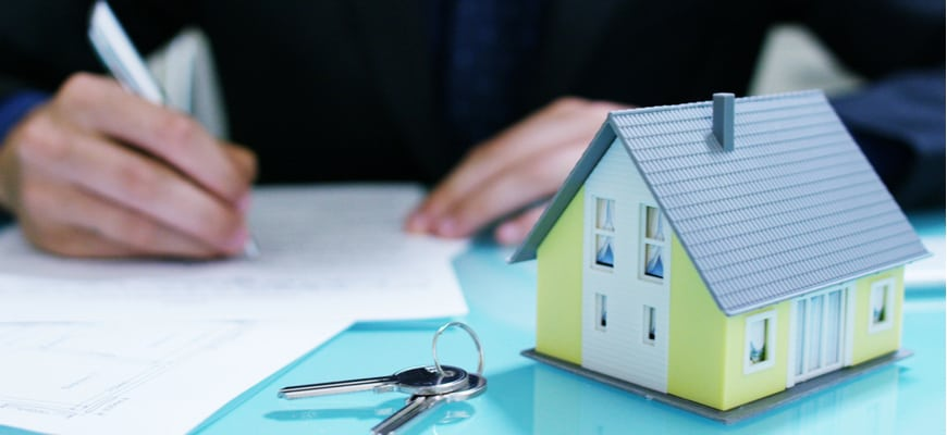 A real estate lawyer signs paper with housekeys in the foreground.